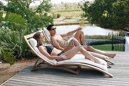 junges paar entspannen auf liegestuhl am