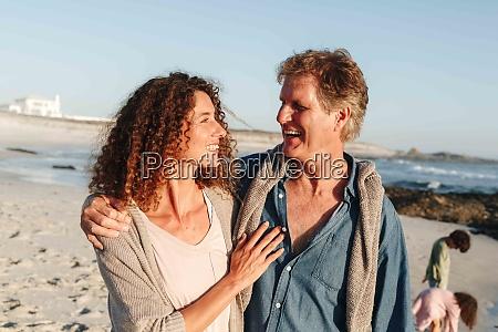 couple taking walk on sandy beach