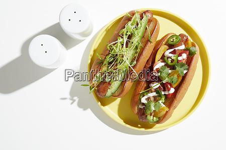 zwei, garnierte, hotdogs, auf, gelber, platte, Überkopf - 27459198
