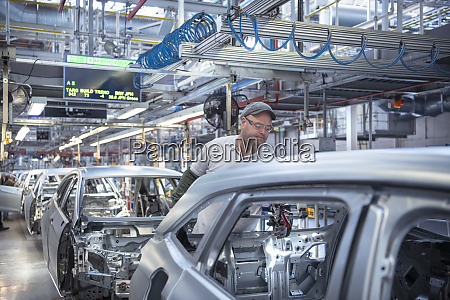 workers on car production line in