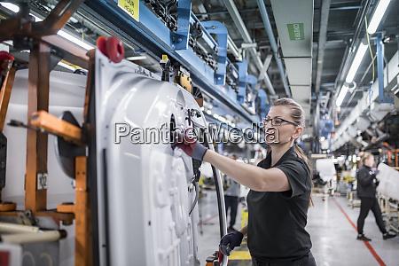 female worker assembling car doors on