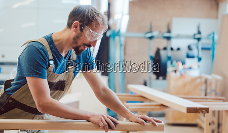 carpenter sanding piece of wood by