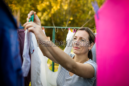 young woman putting laundry on a