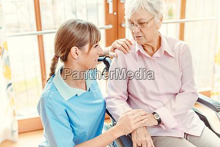 betreuerin und seniorin im pflegeheim