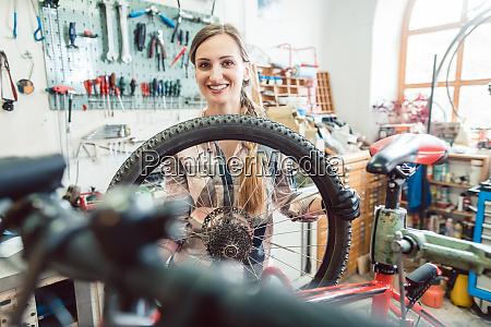 bike mechanic woman looking through the