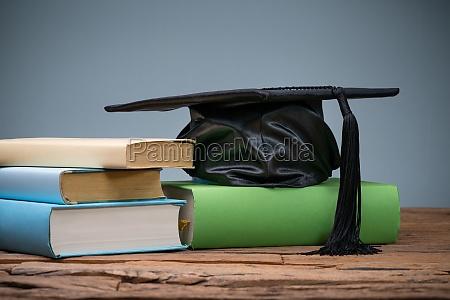 schwarze graduierung hut ueber die buecher