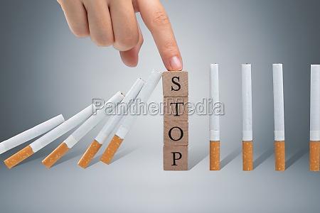 person stoppt zigarette von fallen mit