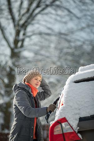 huebsche junge frau reinigt ihr auto