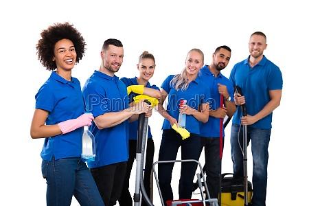 laechelnde multiethnische gruppe von janitoren tragen