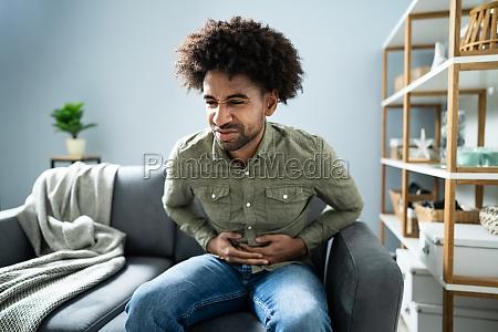 mann mit bauchschmerzen sitzt zu hause