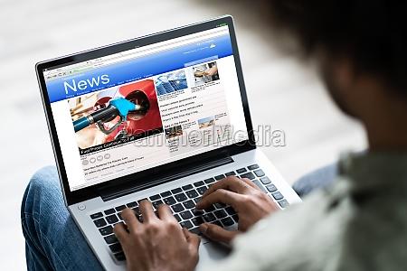mann watching online nachrichten auf laptop