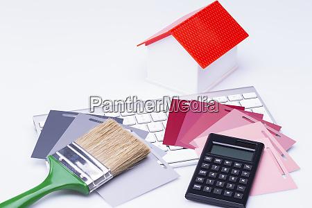 modellhaus mit pinselrechner und farbkarten auf