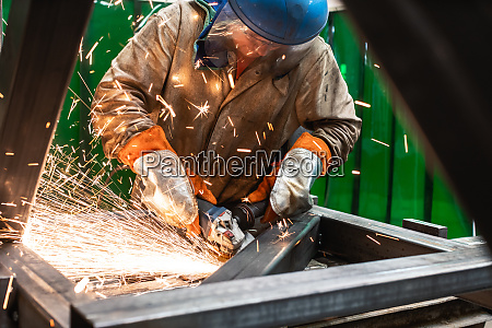 metallbauer arbeitet mit winkelschleifer