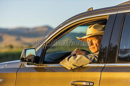 landwirt traegt cowboyhut fahren suv