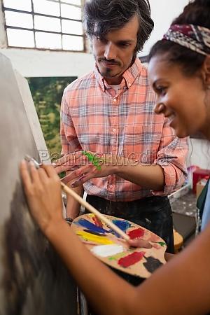 mann hilft frau bei der malerei