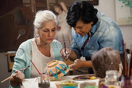 frau hilft seniorin in malschale bei