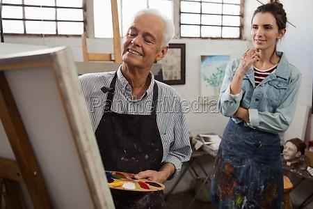 frau beobachtet waehrend senior mann malerei