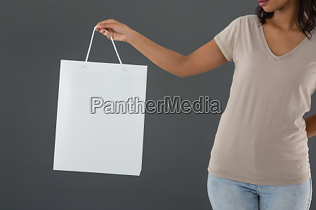 mid section of woman holding shopping