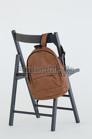 rucksack haengt auf schwarzem stuhl
