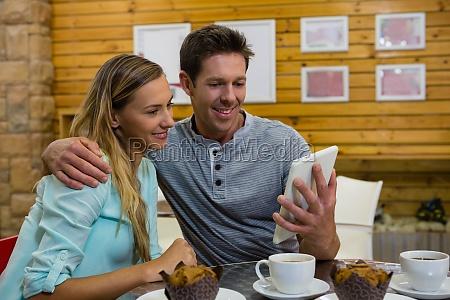 man showing digital tablet to girlfriend