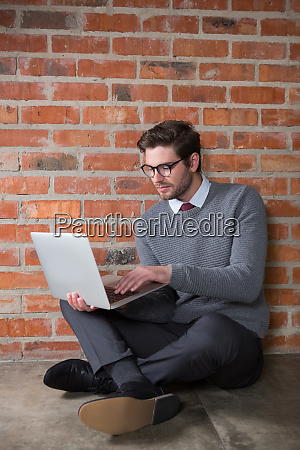 fuehrungskraft mit laptop gegen ziegelwand im