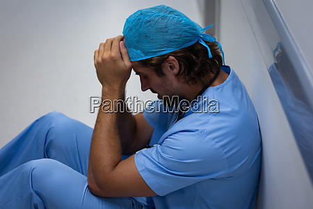 depressed male surgeon sitting and leaning