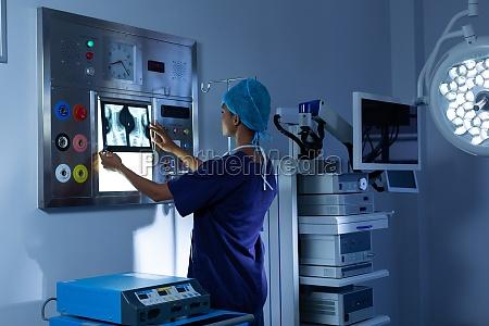 female surgeon examining x ray on
