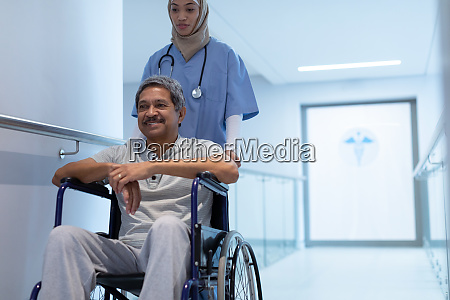 female doctor pushing male patient in