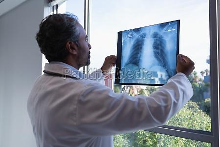 maennlicher arzt mit roentgenbericht in klinik