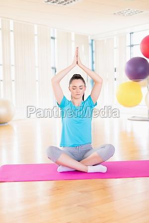 frau die yoga im fitnessstudio durchfuehrt