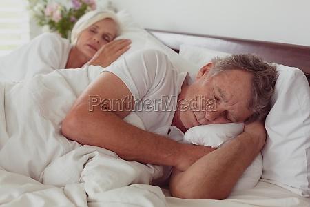 aktives seniorenpaar schlaeft zusammen im bett