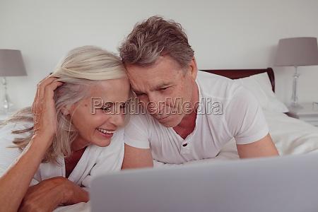 active senior couple using laptop while