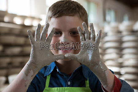 boy showing clay hands in pottery