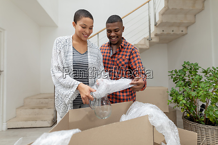 paar packt pappkartons im wohnzimmer aus