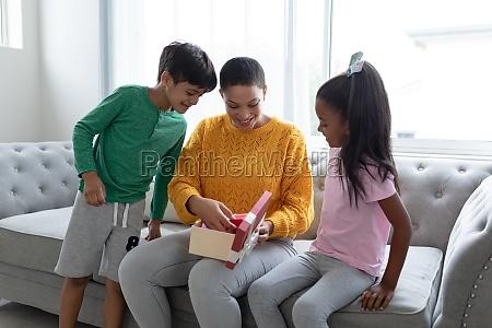 mutter oeffnet eine geschenkbox mit ihren