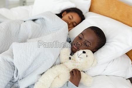 geschwister schlafen zusammen im bett im