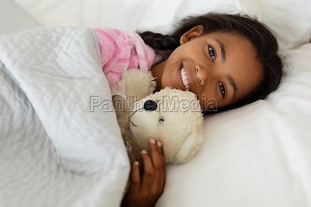 maedchen schlafen mit teddybaer im bett
