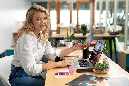 female graphic designer holding a color