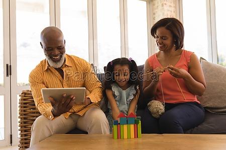 mehrgenerationenfamilie geniesst ihre freizeit im wohnzimmer