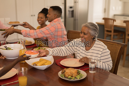 seniorin gibt essen an ihren enkel