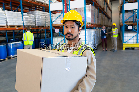 male worker carrying cardboard box and