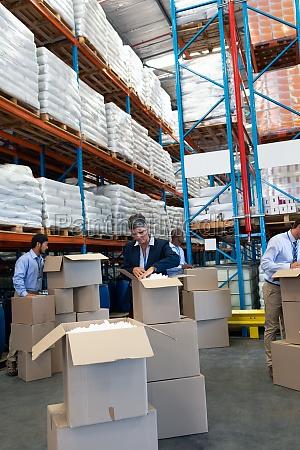 diverse staff unpacking cardboard boxes