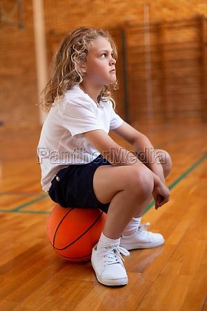 schuelerin sitzt auf einem basketball in