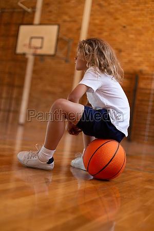 schulmaedchen sitzt auf basketball auf basketballplatz
