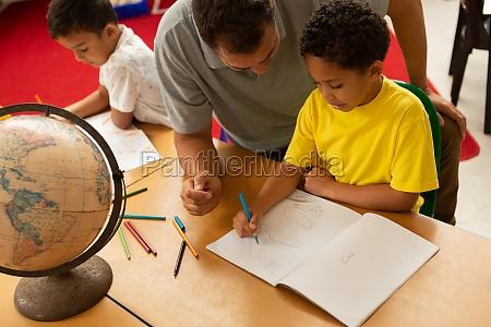 maennlicher lehrer unterrichtet einen schueler in