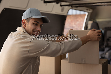 delivery man unloading cardboard boxes from