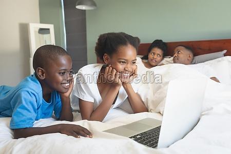 glueckliche afroamerikanische kinder mit laptop waehrend