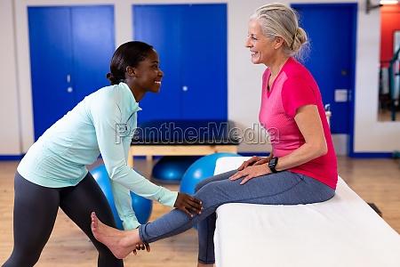 weibliche physiotherapeutin gibt beinmassage an aktive