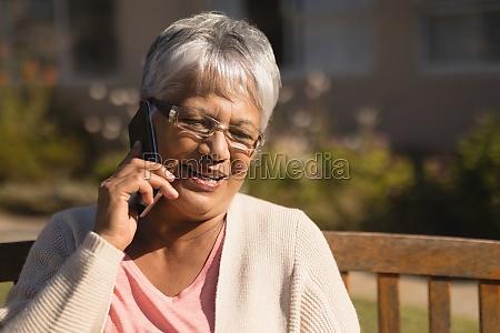 seniorin spricht auf handy im park