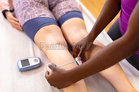 physiotherapeutin mit elektrostimulation auf aktive seniorin